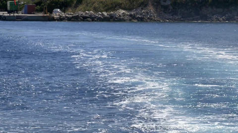 Waves swirling that they leave behind a boat away from the shore of the island i Footage