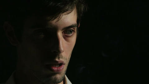 desperate young man on dark background: sad, sadness, smoking, loneliness Live Action
