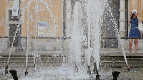 tourist is taking picture to a weird fountain with water games Footage