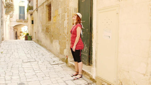 young woman exits from a old house in a little town: tourism, Italy, village Footage