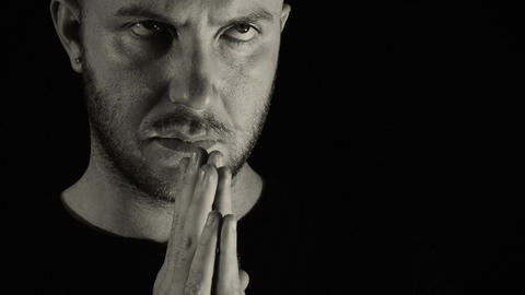 young man praying alone in the darkness: meditation, prayer, emotions, spiritual Live Action