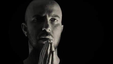young man prays intensely black background, concentration, abstraction, prayer Footage