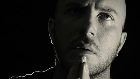 young man prays intensely black background, religion, abstraction, prayer Footage