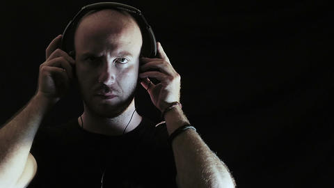 young man wearing headphones to listen to music: sound, loneliness, relaxation Footage