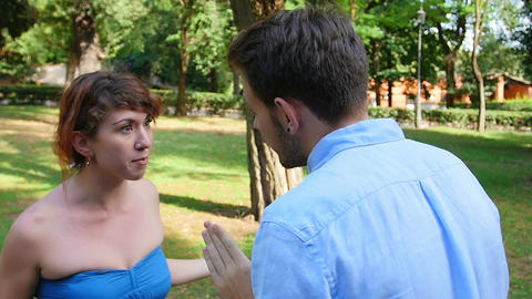 fighting couple in the park: young man and young woman are quarreling Live Action