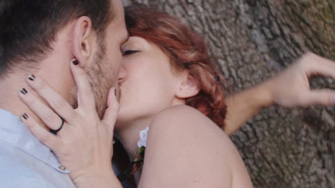 couple in love kissing near a tree: park, love, sex, relationship Footage