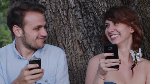 engaged couple chatting with mobile phone at the park Footage
