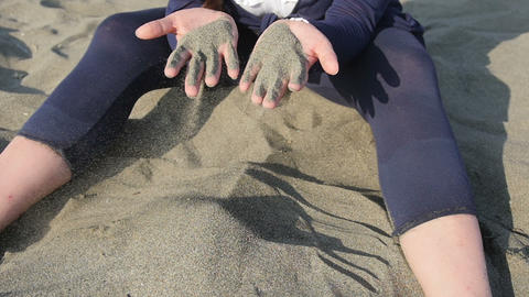 young woman playing with the sand through your fingers at the sea on the beach Footage