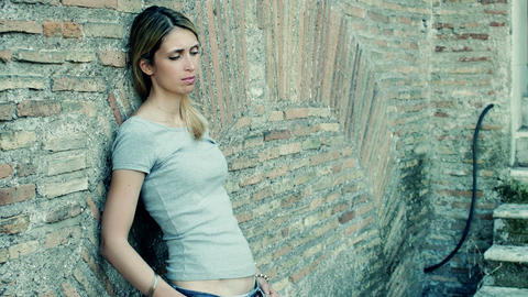 girl sad and pensive leaning against the wall: loneliness, anxiety Live Action
