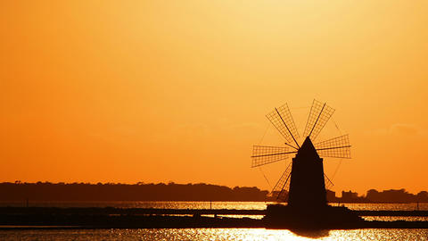 windmill at sunset: sky, sun, yellow, salt pans of Trapani, Sicily, Italy Footage