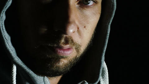 closeup portrait of lonely sad man with hood: anger, isolation Footage
