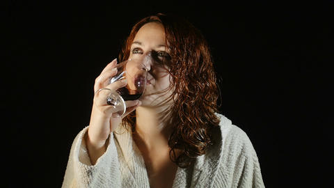 woman drinking red wine in the darkness after a shower: alcoholic, addiction Footage