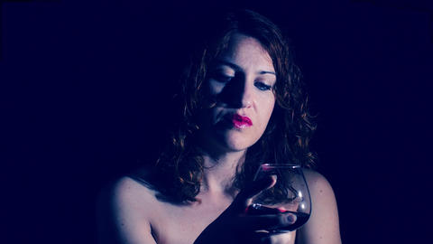 portrait of a woman drinking red wine in the darkness Footage