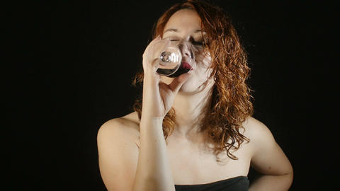 portrait of a woman making a toast and drinking red wine in the darkness Footage