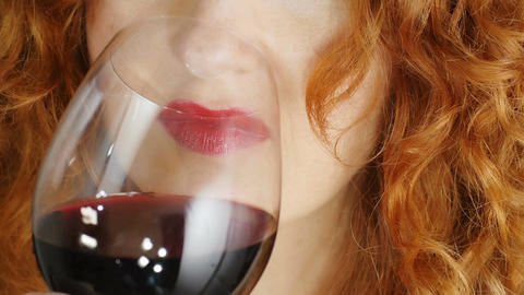 beautiful red haired woman drinking red wine isolated in dark background Footage