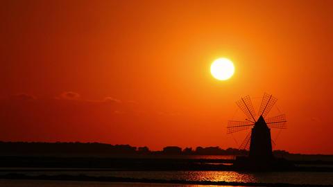 windmill at sunset: sky, sun, yellow, salt pans of Trapani, Sicily, Italy Footage