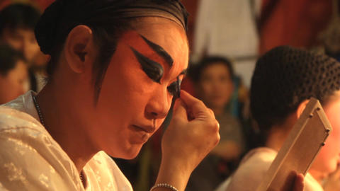 A Chinese opera performer applies make-up 영상물