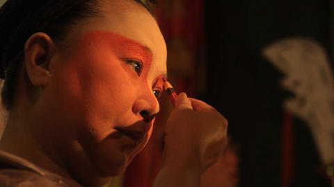 A Chinese opera performer applies make-up Footage