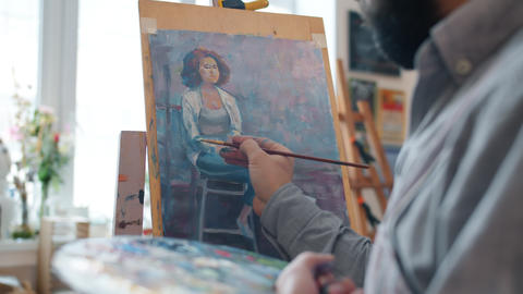 Talented male artist creating portrait of young woman working indoors in Live Action