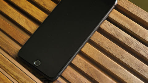 Black cellphone on a wooden table Live Action