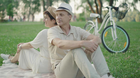 Cheerful mid-adult man and woman sitting back to back on green lawn and talking Live Action