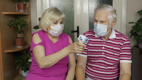 Grandfather and grandmother measures temperature with electronic thermometer Live Action