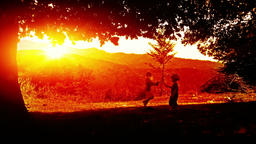 Kids playing, mountain range sunset Footage
