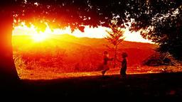 Kids playing, mountain range sunset Footage