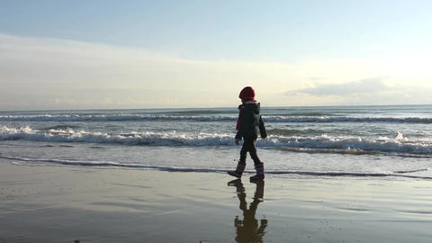 Five-year girl walks along the beach in boots autumn day Footage
