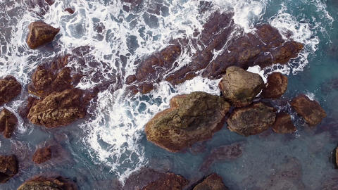 Aerial view of waves splashing on rocky coastline. Top view of big waves hitting Live Action