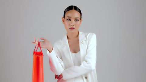 Beautiful Asian modern look businesswoman holding red shopping bag and looking at camera Live Action