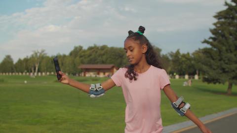 Cute teenage girl on roller blades vlogging online Live Action