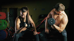 Man and woman working his arms at the gym Footage