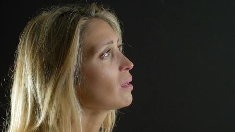 sad woman praying in dark background: sadness, crying, melancholy Live Action