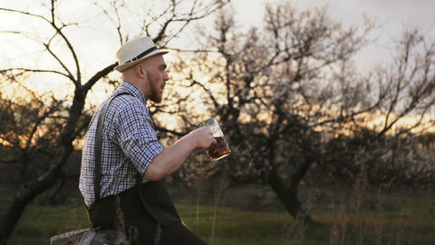 Man sitting on a stump and enjoying tasty beer Footage