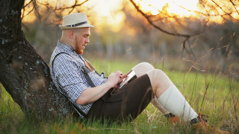 Stylish young man in the park with tablet in hands Footage