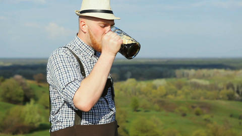 A man in a spring day enjoying a delicious dark beer Footage