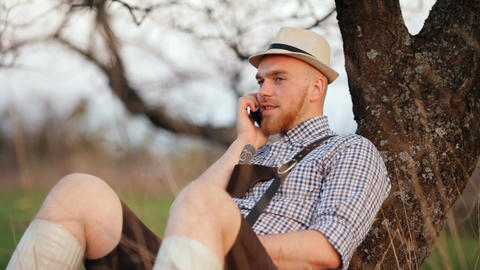 Man outdoors sitting on grass talking on a smartphone GIF