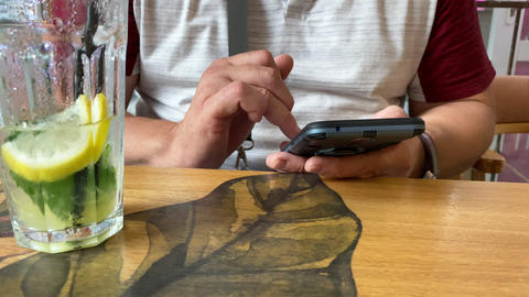 adult man sits at a table in a cafe and looks at the smartphone screen, touches the touch screen Live Action