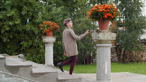 Teenager girl walking in downstairs in country house to green garden with Live Action