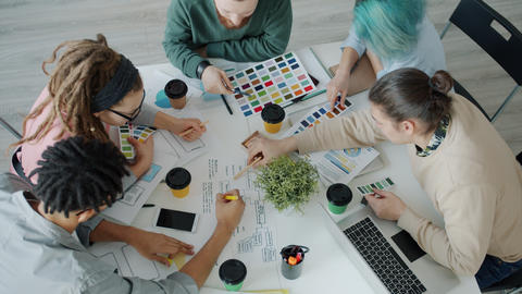 Smartphone application designers choosing colors for project talking in office Live Action