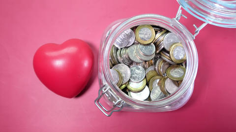 Red heart and coins in a jar on red background Live Action