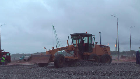 Grader leveling gravel on construction site Footage