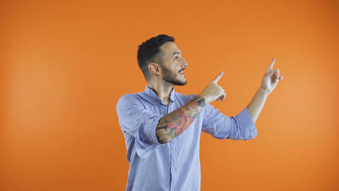 Black haired man pointing with fingers up at invisible product, isolated on Live Action