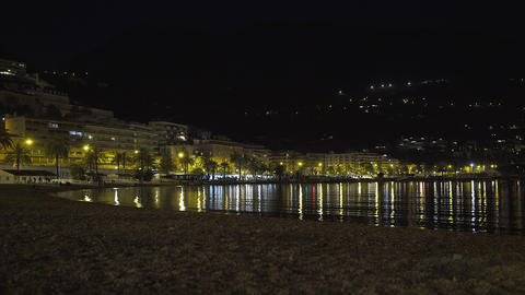 Night panoramic view of the illuminated beach and the town of Menton Live Action