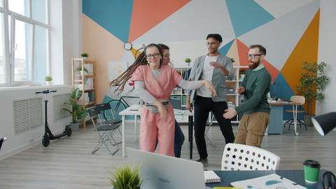 Carefree office workers girl and guys dancing in workplace having fun together Live Action