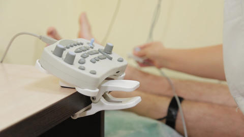 Woman doctor clicks on a device to measure nerve impulses Live Action