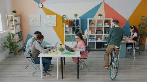Young man coming to work by bike then talking to colleagues working in office Live Action