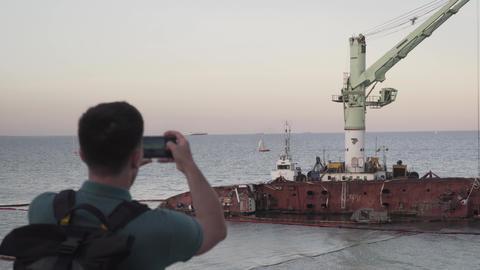 Male blogger is broadcasting live on social networks on journey near sunken Live Action