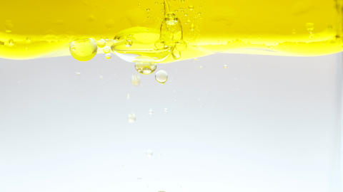 Oil drops splashing into water - close-up Live Action